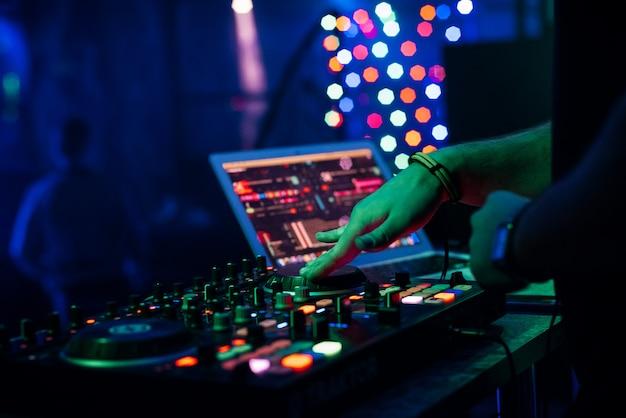 Dj reproduce música en un mezclador controlador de equipos de música profesional