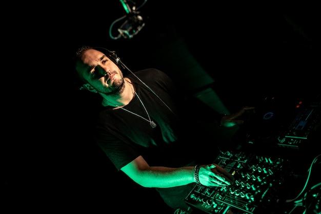 Dj tocando house y techno en un club nocturno. mezclando y controlando la música.