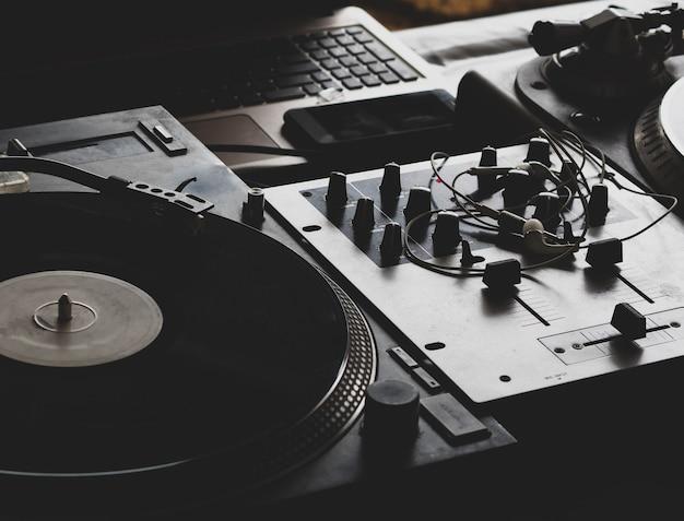 Dj tocando música en una fiesta de hip hop. tocadiscos analógico, dj usa tocadiscos y mezclador para hacer scratch.
