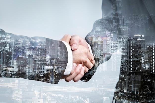 Doble exposición de apretón de manos de asociación comercial y ciudad moderna, saludo o acuerdo comercial exitoso después de un trato perfecto