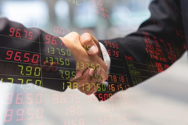 Doble exposición del apretón de manos del hombre de negocios y de la empresaria para la carta del indicador del socio y del precio del mercado de valores, concepto del negocio.