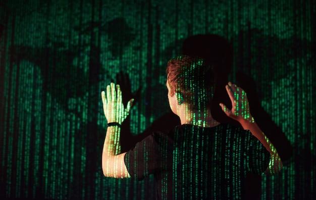 La doble exposición de un hombre caucásico y un casco de realidad virtual vr es presumiblemente un jugador o un pirata informático que descifra el código en una red o servidor seguro, con líneas de código, estados unidos