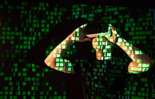 La doble exposición de un hombre caucásico y un casco de realidad virtual vr es presumiblemente un jugador o un pirata informático que descifra el código en una red o servidor seguro, con líneas de código en verde.