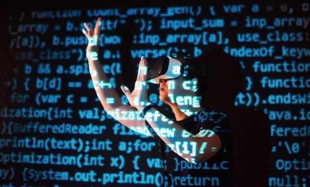 La doble exposición de un hombre caucásico y un casco de realidad virtual vr es presumiblemente un jugador o un pirata informático que descifra el código en una red o servidor seguro, con líneas de código.