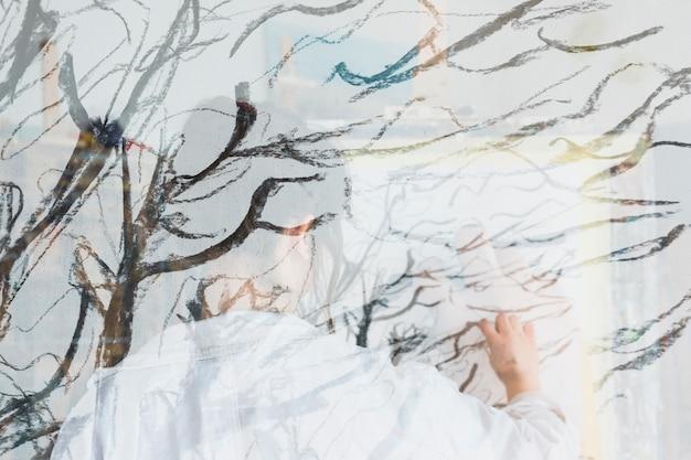 Doble exposición de mujer dibujando sobre lienzo.