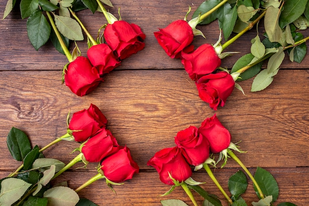 Doce rosas rojas en la mesa de madera con espacio de copia en forma de marco