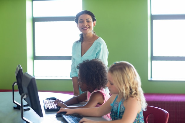 Docente con niños en clase de informática