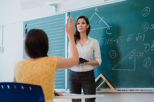 Docente o docente o educador dando una lección frente a un pizarrón o pizarra en una hoja de papel y educar o enseñar a los estudiantes o alumnos o compañeros en una escuela o clase