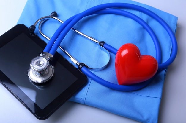 Doctor abrigo con estetoscopio médico y corazón rojo sobre el escritorio