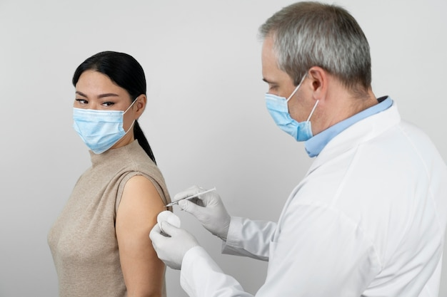 Doctor administrando vacuna inyectada a paciente