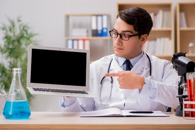 Doctor adulto joven con ordenador portátil