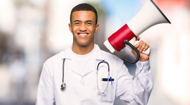 Doctor afroamericano joven del hombre que sostiene un megáfono en al aire libre
