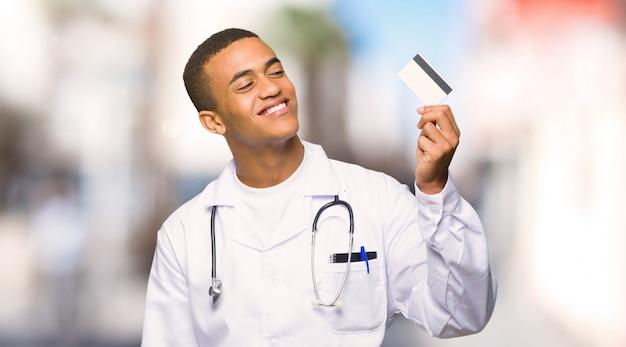 Doctor afroamericano joven del hombre que sostiene una tarjeta de crédito y que piensa en al aire libre