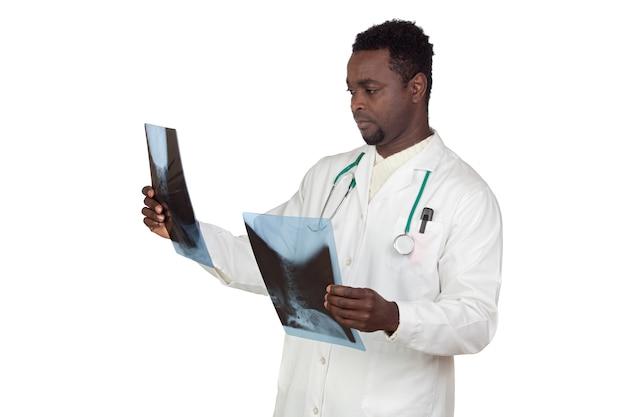 Doctor afroamericano que mira una radiografía aislada en un fondo blanco excesivo