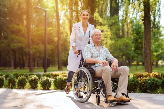 Doctor con anciano en silla de ruedas caminando en el parque soleado