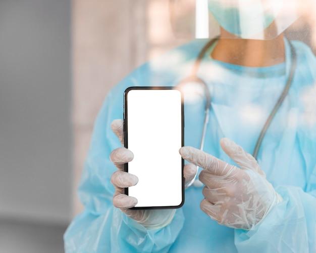 Doctor apuntando a un teléfono inteligente de pantalla vacía