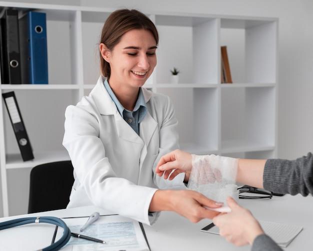 Doctor arreglando la servidumbre de la mano para el paciente
