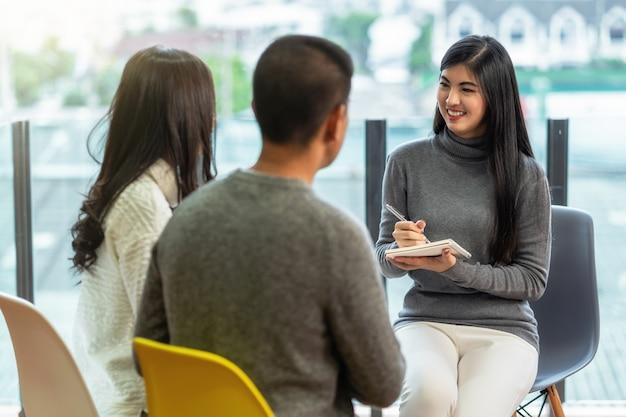 Doctor asiático del psicólogo profesional de la mujer que da la consulta a los pacientes de los amantes