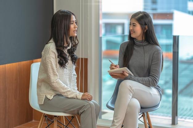 Doctor asiático del psicólogo profesional de la mujer que da la consulta a los pacientes femeninos en sala de estar