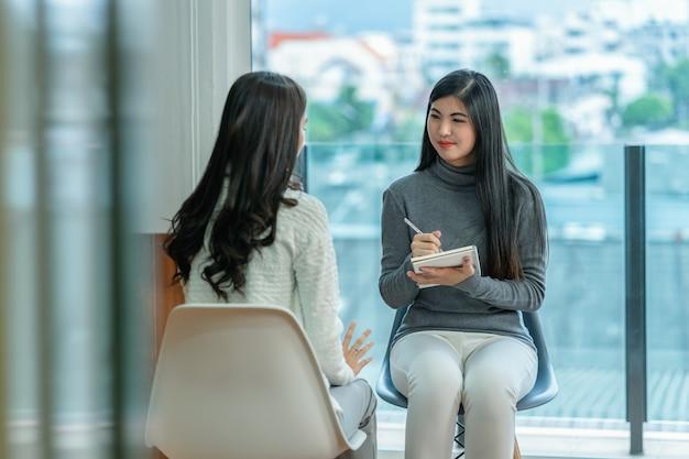 Doctor asiático del psicólogo profesional de la mujer que da la consulta a los pacientes femeninos