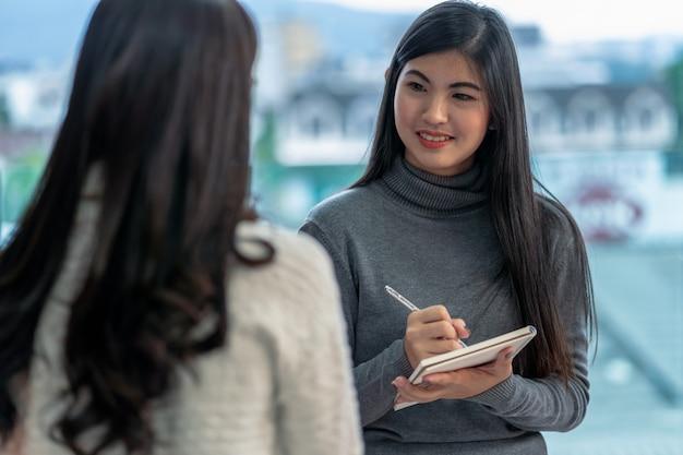 Doctor asiático del psicólogo profesional de la mujer que da la consulta a los pacientes en sala de estar