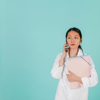 Doctor asiático respondiendo llamada telefónica
