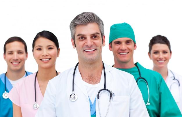 Doctor atractivo con su equipo detrás de él.