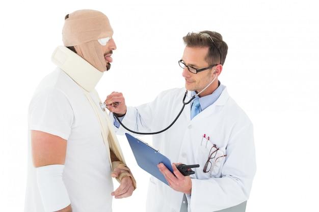 Doctor auscultando paciente atado en vendaje con estetoscopio