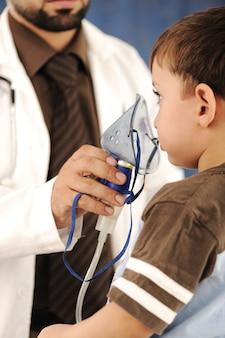 El doctor está auxiliando a un chico con una máscara de oxígeno