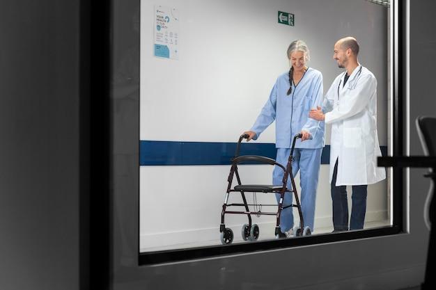 Doctor ayudando al paciente a caminar