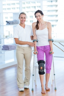 Doctor ayudando a una mujer caminando con muletas