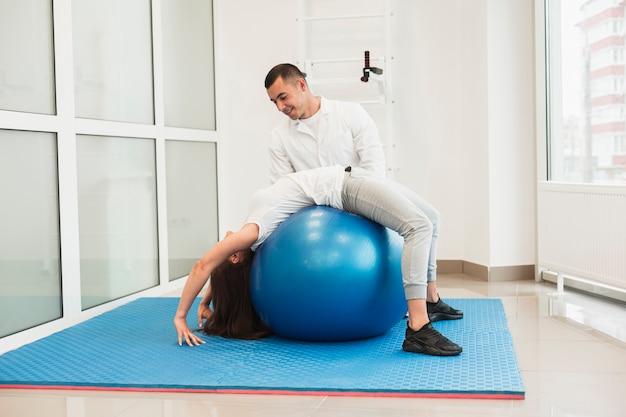 Doctor ayudando a paciente con balón terapéutico