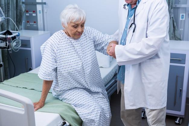 Doctor ayudando a paciente senior en el hospital