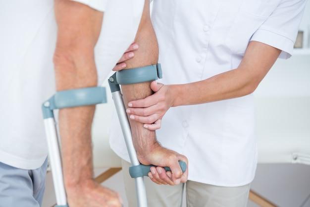 Doctor ayudando a su paciente a caminar con muleta