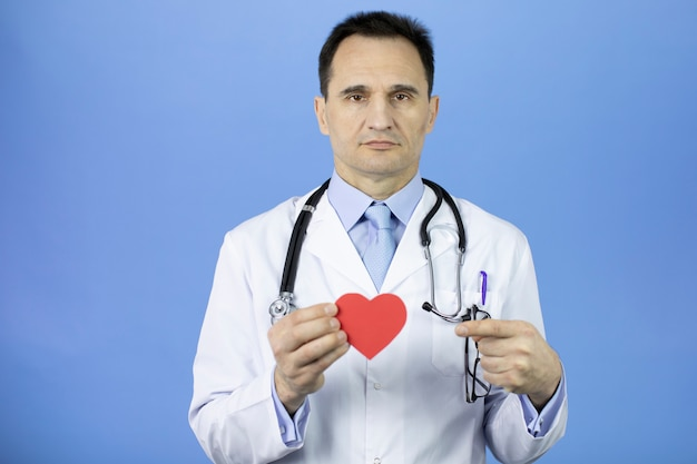 Doctor en azul sostiene el corazón en las manos, apunta con el dedo índice