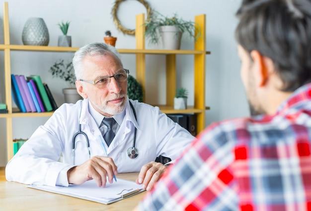 Doctor barbudo escuchando paciente