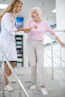 Doctor en bata de laboratorio apoyando a su paciente en las escaleras y luciendo amigable