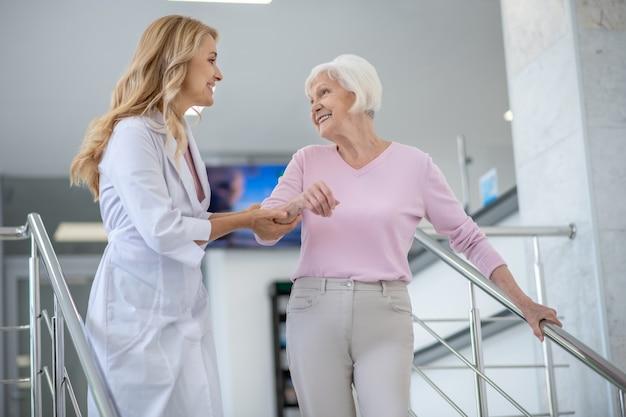 Doctor en una bata de laboratorio apoyando a su paciente y sonriendo