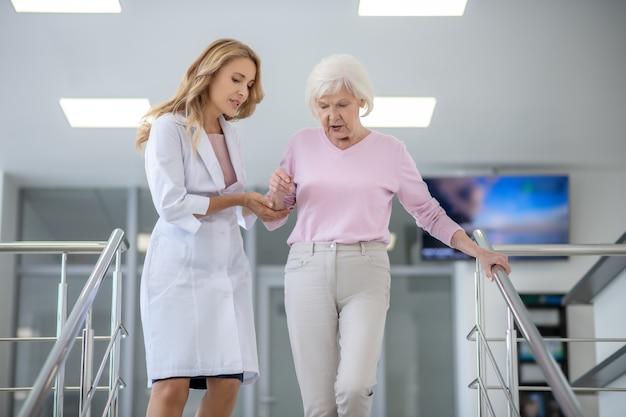 Doctor en una bata de laboratorio ayudando a una mujer en las escaleras