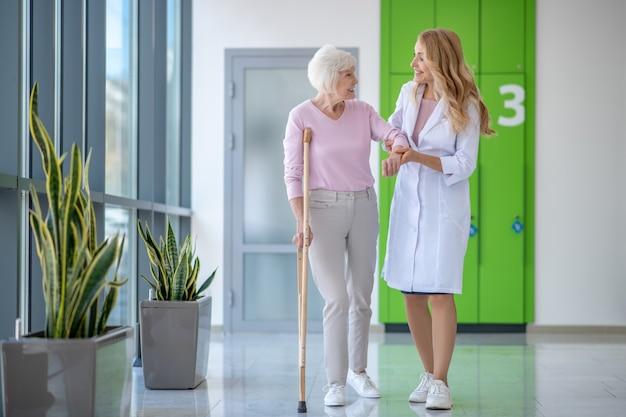 Doctor en una bata de laboratorio y un paciente caminando juntos y hablando