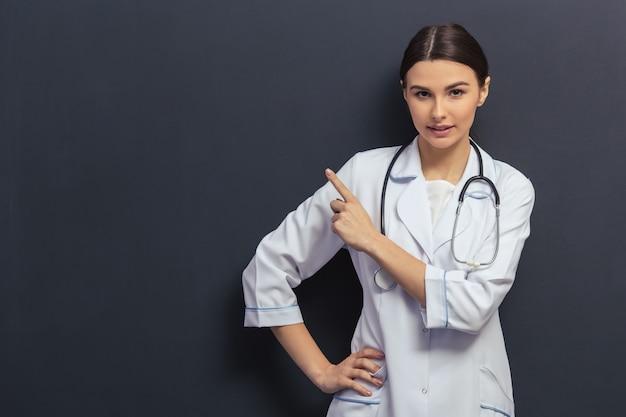 Doctor en bata médica blanca está apuntando lejos.