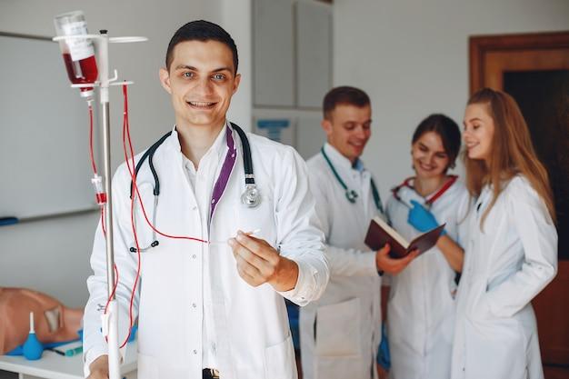 Doctor en bata tiene un gotero con medicamentos