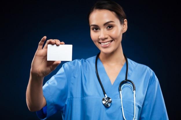 Doctor bonito que muestra la tarjeta de identificación en blanco o tarjeta de visita y sonriendo