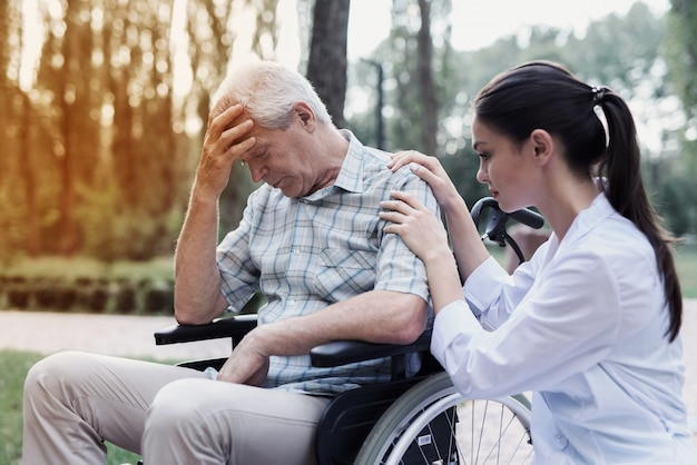 El doctor calma al abatido anciano en una silla de ruedas