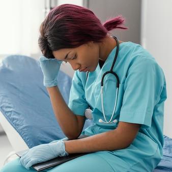 Doctor cansado de tiro medio sentado