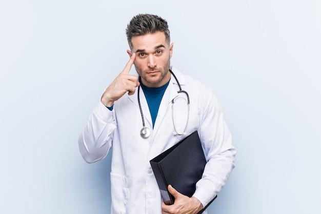 Doctor caucásico hombre sosteniendo una carpeta señalando su sien con el dedo, pensando, centrado en una tarea.
