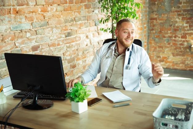 Doctor caucásico que consulta para el paciente, trabajando en gabinete