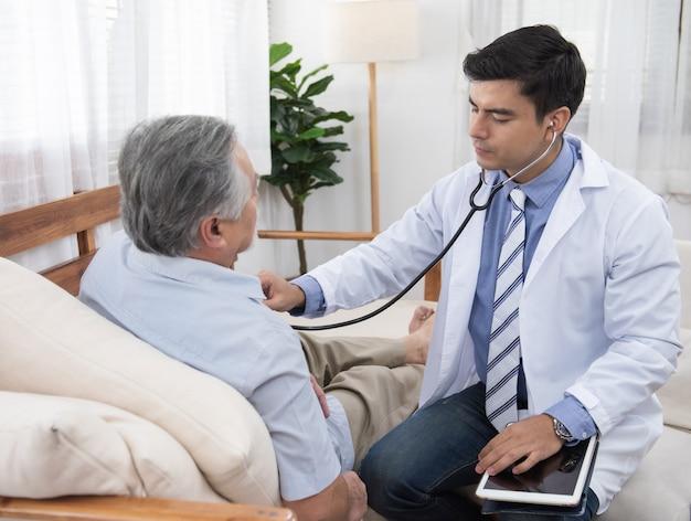 El doctor caucásico se sienta en la silla comprueba el latido cardíaco asiático mayor mayor del viejo hombre que se acuesta en el sofá en casa.