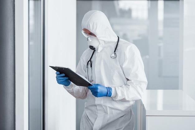 Doctor científico masculino en bata de laboratorio, gafas defensivas y máscara con bloc de notas en las manos