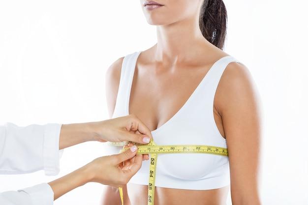 Doctor con cinta métrica que mide el tamaño del pecho del paciente.